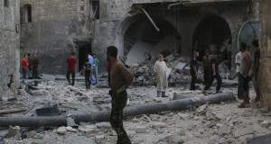 People inspect a site hit by what activists said was an airstrike by forces loyal to Syria's President Bashar al-Assad in Qadi Askar district in Aleppo